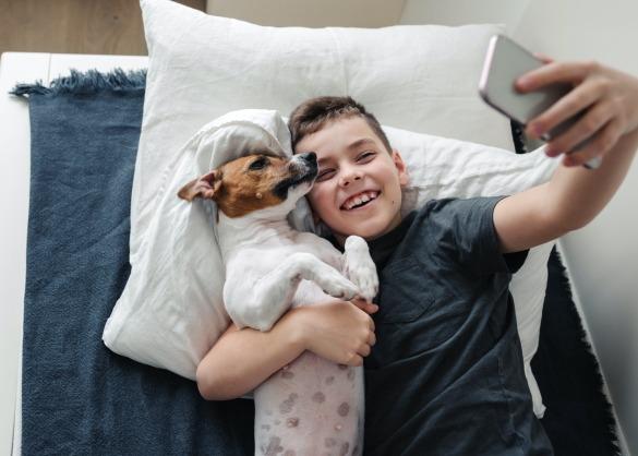 Jongen maakt selfie met hondje op bed