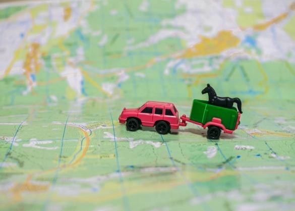 Speelgoedauto met paardentrailer op wereldkaart