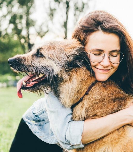 Jonge vrouw knuffelt met oude hond