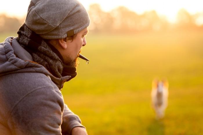 Man roept hond met fluitje, hond komt aangelopen op de achtergrond