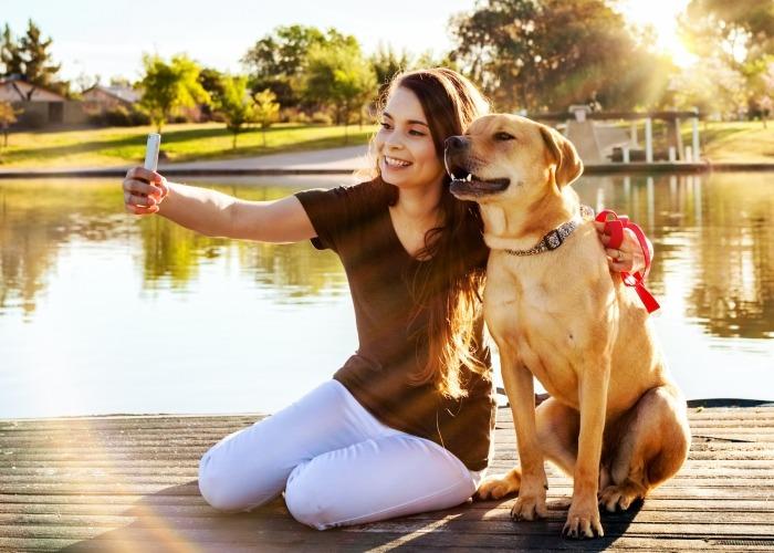 Vrouw maakt selfie met hond bij water