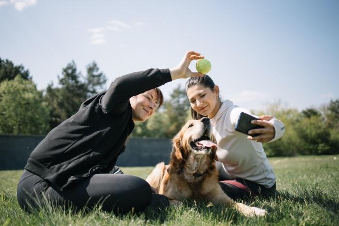 Twee vrouwen maken selfie met hond en tennisbal