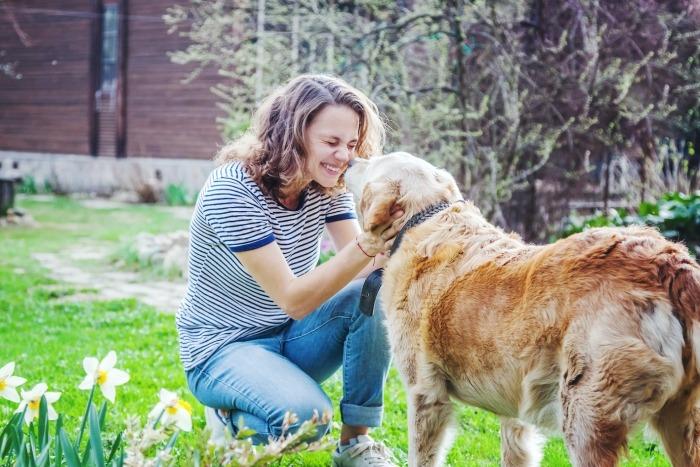 Jonge vrouw aait oude hond