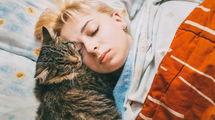 Kat slaapt op vrouw